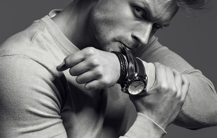Advertising wrist watch concept. Beautiful (handsome) muscular male model with perfect body in grey jumper. He bites and unfastens th_110095661_XS