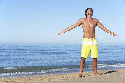 Young Man Standing On Summer Beach_84419817_XS
