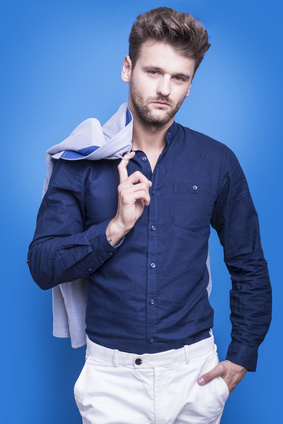 Handsome man in a dark blue shirt on a blue background_115062699_XS