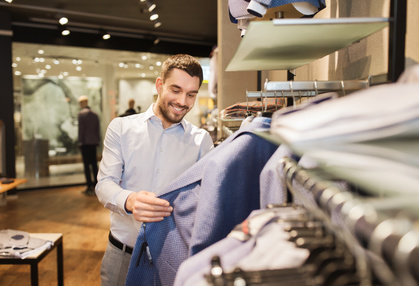 Happy young man choosing clothes in clothing store_111678258_XS
